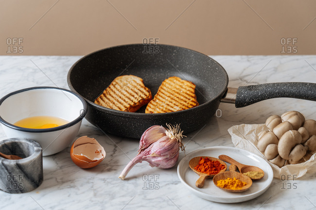 Frying pan with grilled toast and ingredients on gray surface