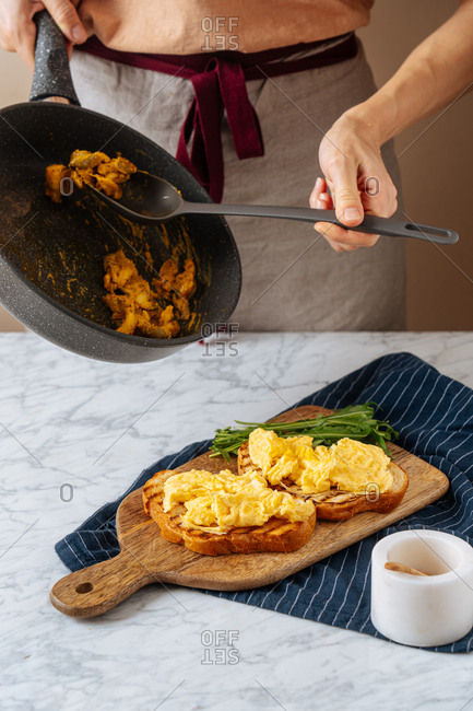 Chef scooping ingredients from skillet onto grilled toast with eggs