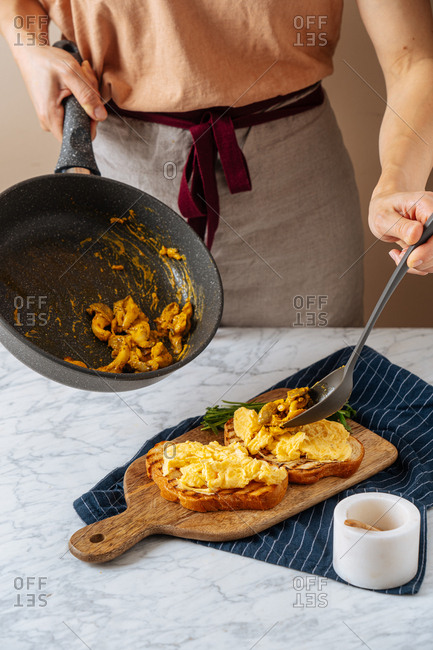 Woman scooping ingredients from skillet onto grilled toast with eggs