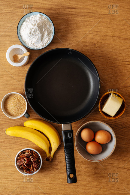 Top view of skillet and ingredients on wooden surface