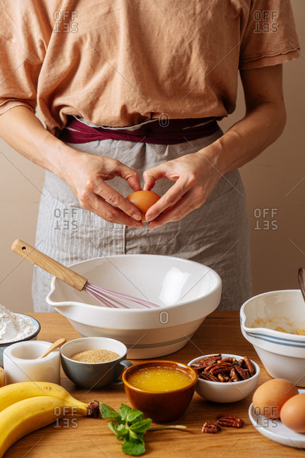Chef breaking an egg while preparing a recipe