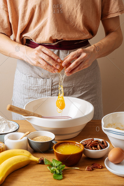 Chef adding an egg into a bowl while preparing a recipe