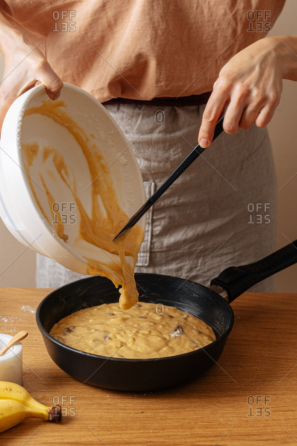 Woman using spatula to pour mixed ingredients into a skillet
