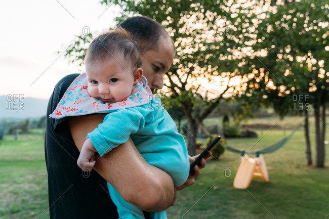 Multitasking father holding a baby girl with one hand while using mobile phone with other hand outdoors