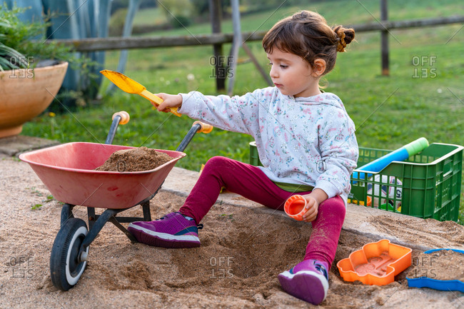 Three years old baby girl playing with a sand shovel and wheelbarrow in a sandpit outdoors