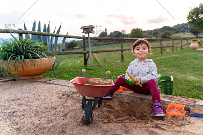 Cute toddler playing with a sand in a sandpit looking at camera