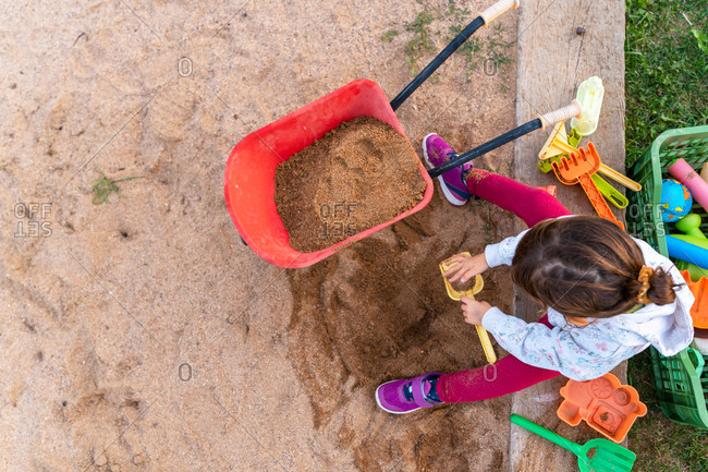 Overhead view of toddler playing with a sand shovel and wheelbarrow in a sandpit outdoors