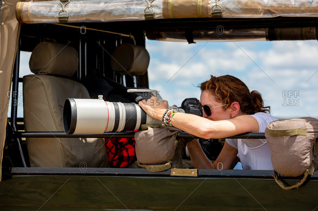 Female professional photographer on safari. Woman rests camera on a bean bag and shoots wildlife from a safari vehicle.  in the Masai Mara, Kenya.