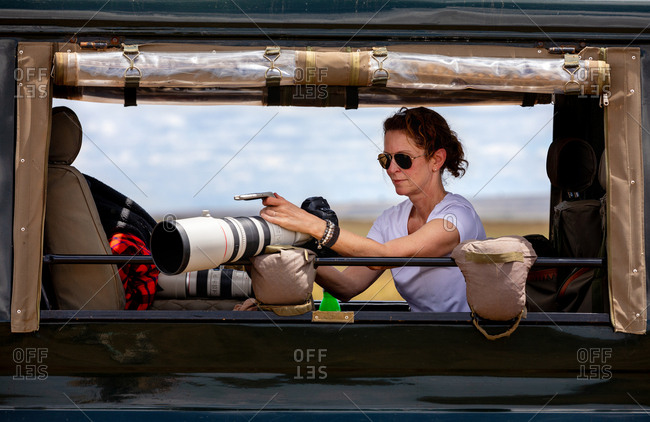 Female professional photographer on safari. Woman rests camera on a bean bag and shoots wildlife from a safari vehicle.  in the Masai Mara, Kenya. Here she is checking images and settings from the camera screen.