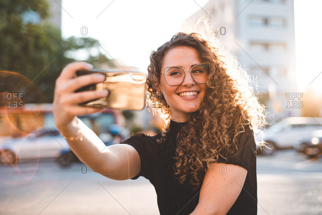 Woman with curly hair sitting on streetside taking selfie in Barcelona in evening light