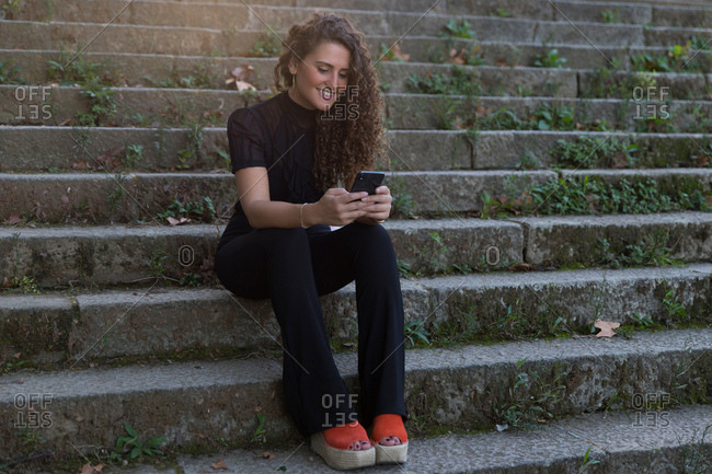 Woman with curly hair sitting on stone steps using her mobile phone