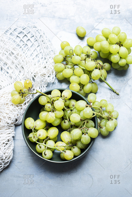 Close up of green grapes lying close to net bag