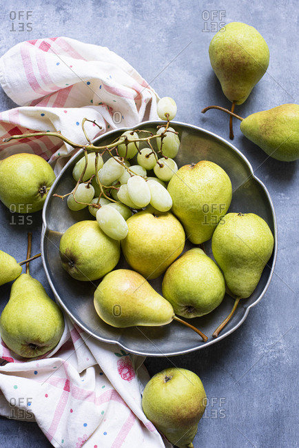 Fresh pears and grapes in metal bowl