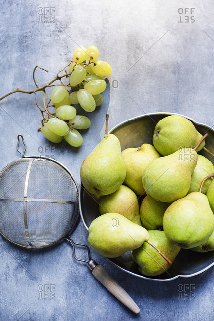 Green pears in metal bowl and  grapes on a side