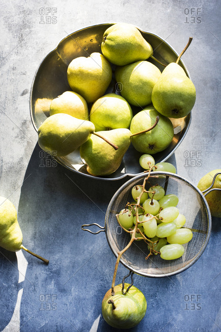 Pears in metal bowl with green grapes in vintage strainer