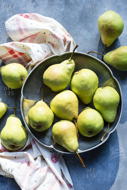 Still life of pears in metal bowl in sunlight