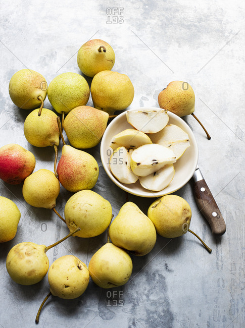 Whole pears with sliced pears in a bowl