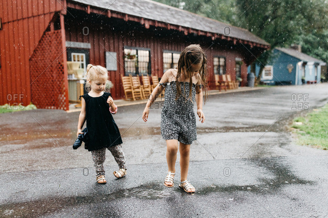 Two little girls playing in the rain