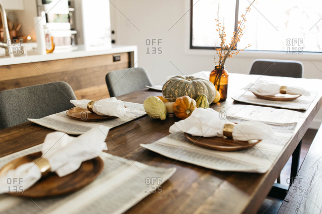 Thanksgiving table set with decorative pumpkins in center