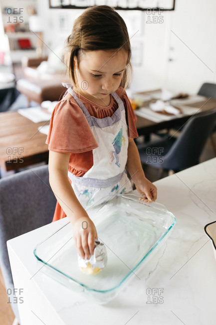 Little girl buttering glass dish while baking