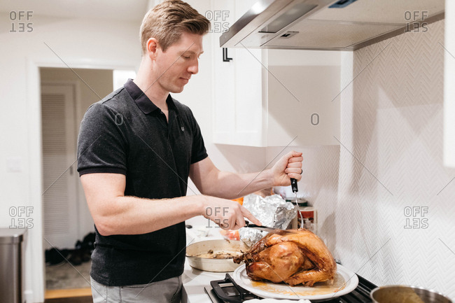 Man carving a Thanksgiving turkey in the kitchen