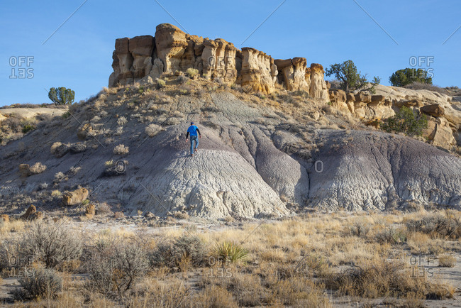Person hiking among Bisti/De-Na-Zin Wilderness hoodoo sandstone formations, New Mexico