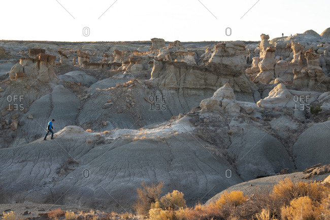 Man hiking on hoodoo sandstone formations in New Mexico's Bisti/De-Na-Zin Wilderness Area