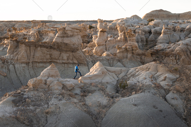 Person hiking on hoodoo sandstone formations in New Mexico's Bisti/De-Na-Zin Wilderness Area