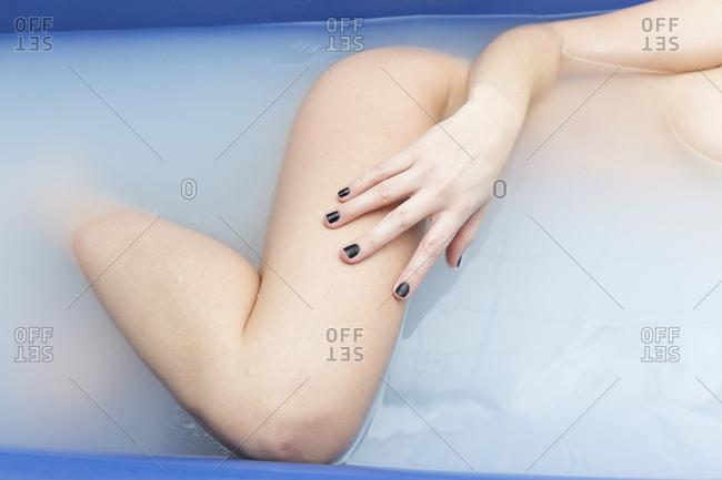 Sensual woman posing in blue bathtub with milky water
