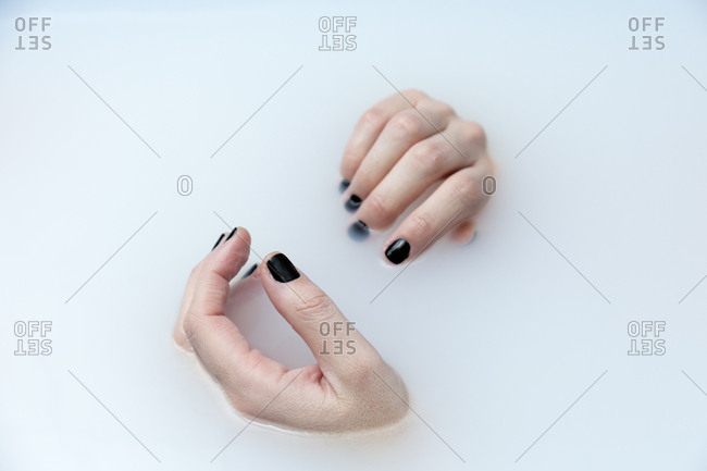 A woman's hands with black fingernail in bathtub with milk