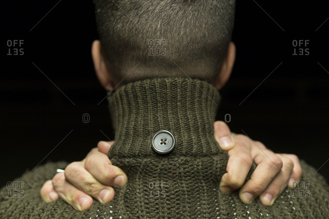 Rear view of a man grasping his shoulders