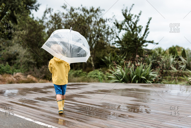 Child in yellow rain jacket holding an umbrella