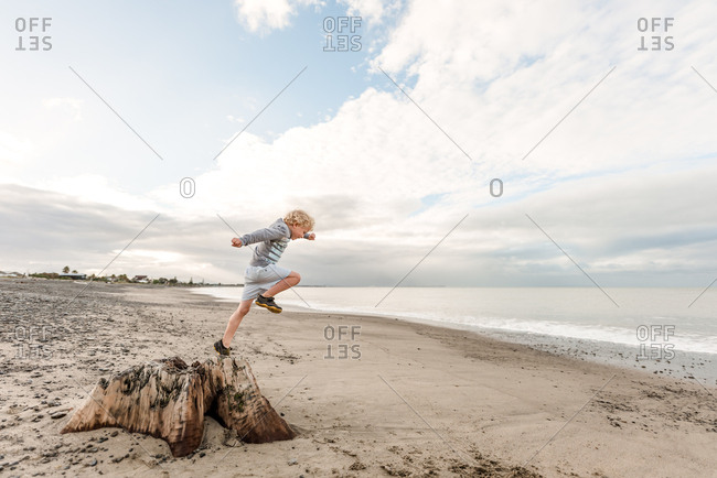 Young boy jumping off of stump at beach