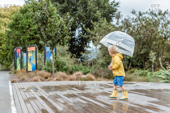 Child wearing rain boots and holding umbrella