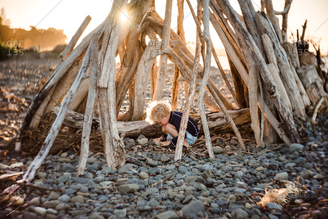 Small child playing in driftwood structure at dusk