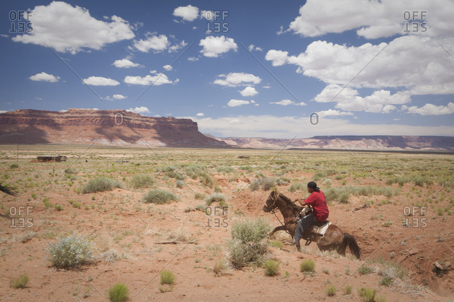 United States, Arizona, Oljato-Monument Valley - June 26, 2010: A young man rides a horse across a plain near Monument Valley, Arizona