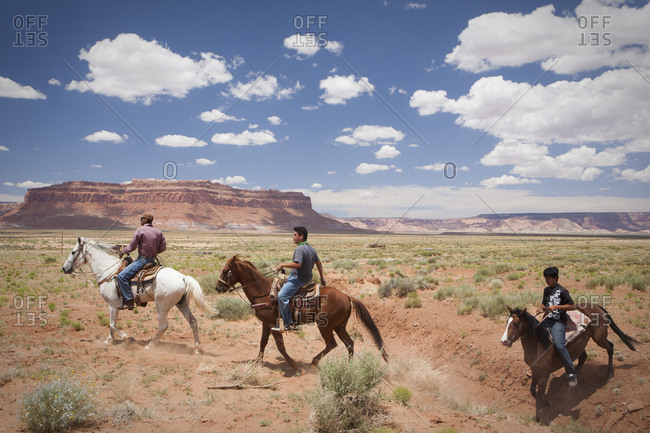 United States, Arizona, Oljato-Monument Valley - June 26, 2010: Horseback riders cross a plain near Monument Valley, Arizona