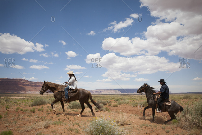 United States, Arizona, Oljato-Monument Valley - June 26, 2010: Cowboys cross an open plain near Monument Valley, Arizona