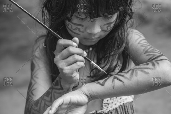 Brazil, State of Amazonas - August 13, 2016: Young indigenous girl from Brazilian Amazon painting her body