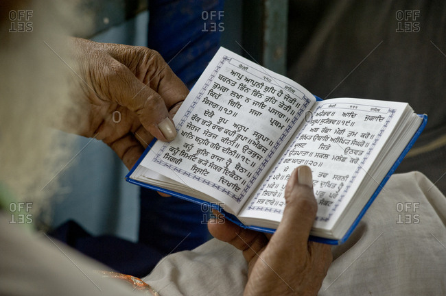 India, Punjab, Amritsar - August 4, 2011: Old Sikh man in reads religious book in the train