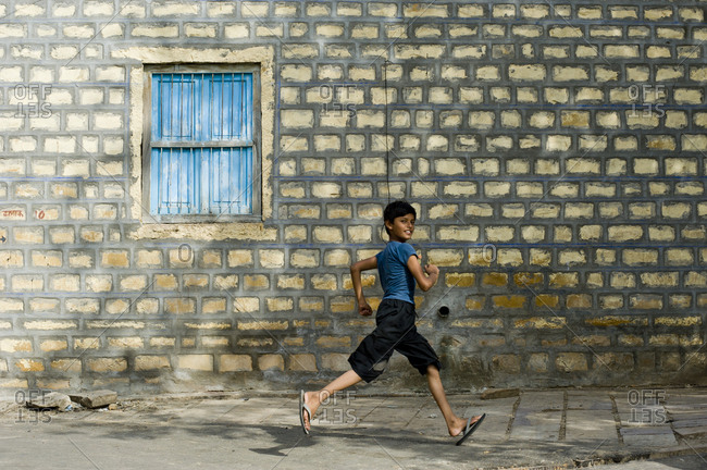 India, Rajasthan, Jaisalmer - August 17, 2011: Beautiful boy running in the streets of Jaisalmer