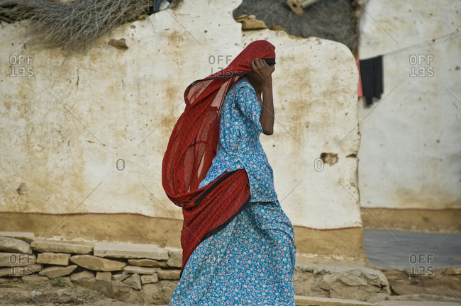 Traditional Rajastan woman walking in a typical village of Jaisalmer