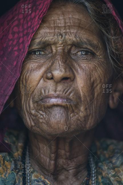 India, Rajasthan, Jaisalmer - August 15, 2011: Old Rajasthan`s woman looking at camera