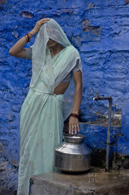 India, Rajasthan, Jodhpur - August 28, 2011: Rajasthan`s woman wearing sari catches water in a faucet