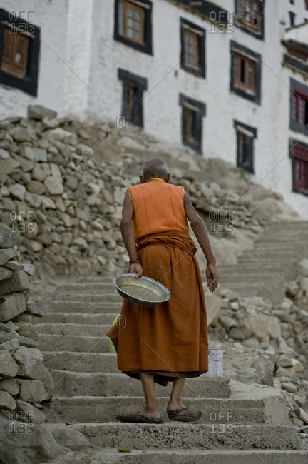 Old monk carrying a tray walking up the monastery ladder