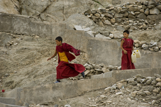 Leh, Jammu and Kashmir, India - July 25, 2011: Young monk runs after the ball down the hill, observed by partner