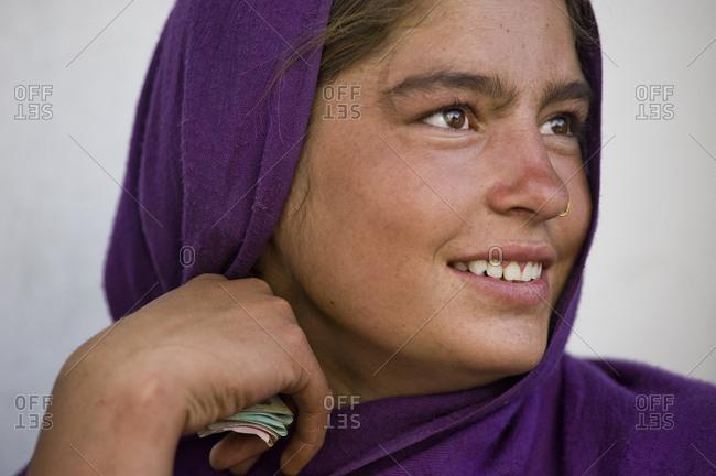 Leh, Jammu and Kashmir, India - July 24, 2011: Beautiful young woman with purple headscarf