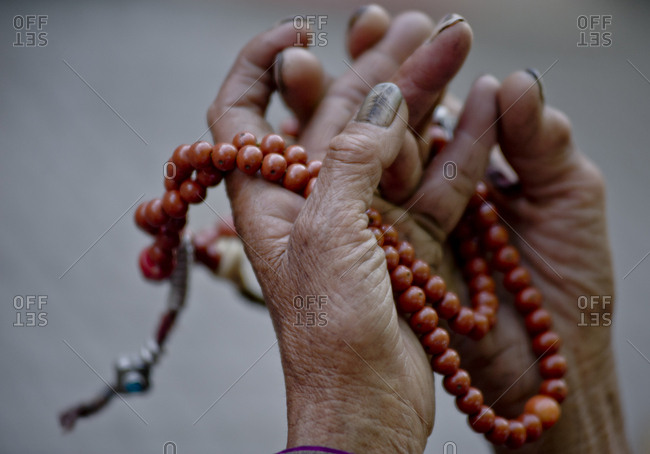 Old woman hands holding a japamala during worship