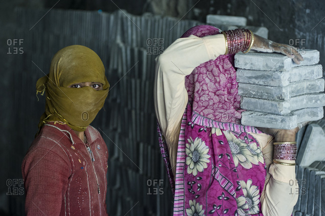 Leh, Jammu and Kashmir, India - July 25, 2011: Female Indian workers carrying heavy construction material