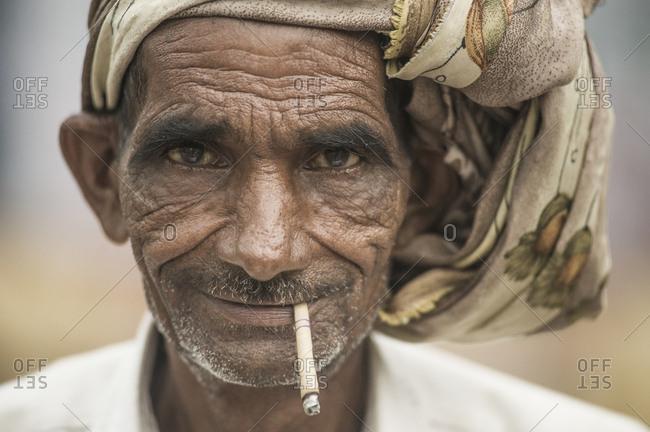 India, Uttarakhand, Rishikesh - July 16, 2011: Old hindu man smoking straw cigarette